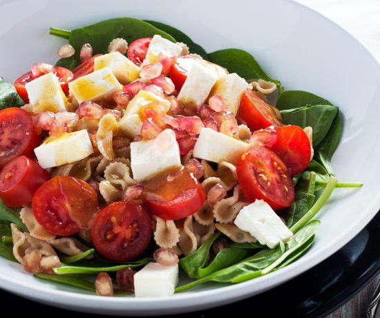 Sałatka z makaronem, serem typu greckiego, szpinakiem i granatem i z sosem