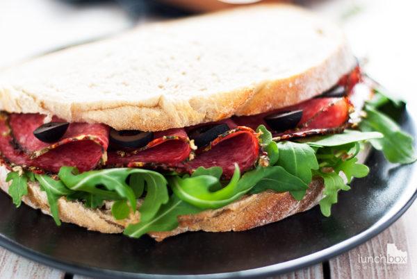 Kanapka z salami, rukolą i oliwkami - z bliska | lunchboxodkuchni.pl